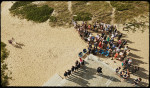 bird's eye view of bride and groom walking towards lighthouse ceremony on martha's vineyard