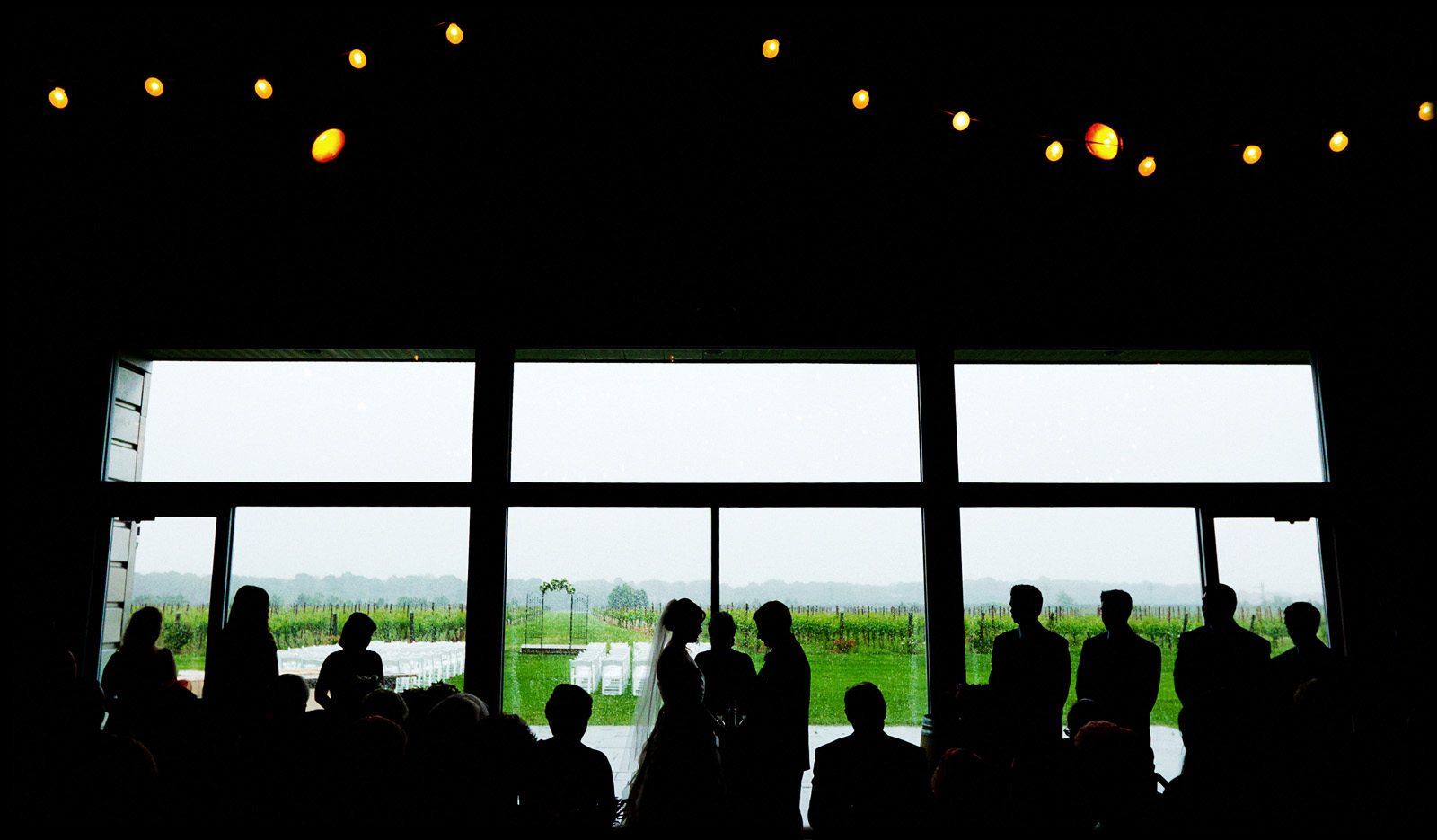 couple exchanges vows in front of rainy vineyard in virginia