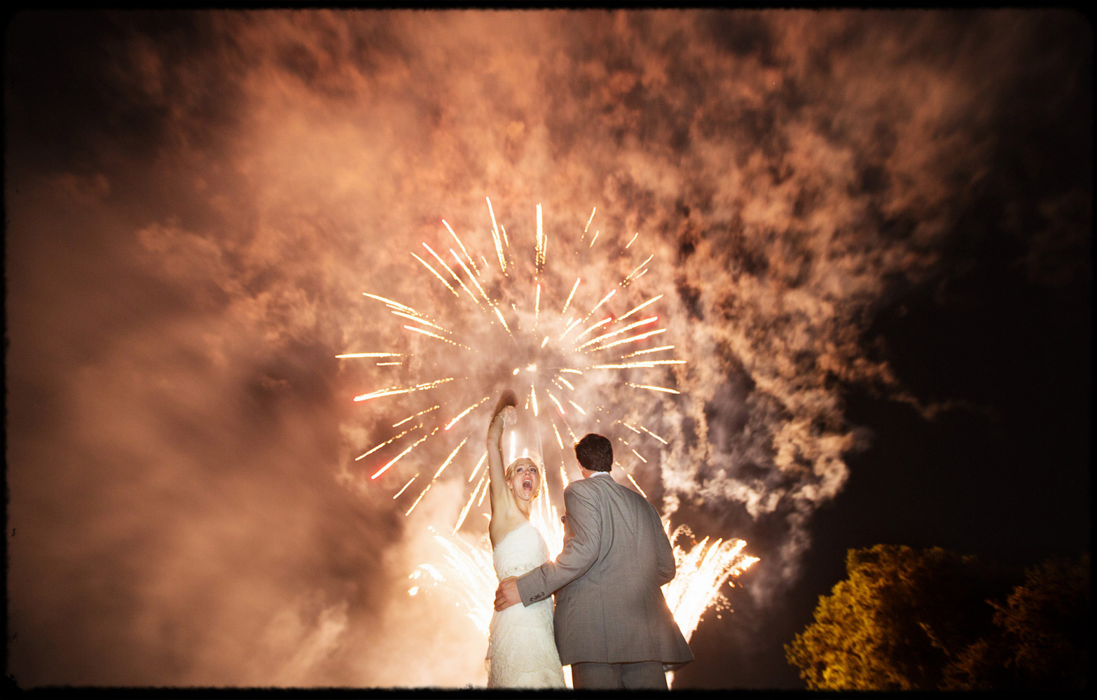 cheering couple during wedding fireworks