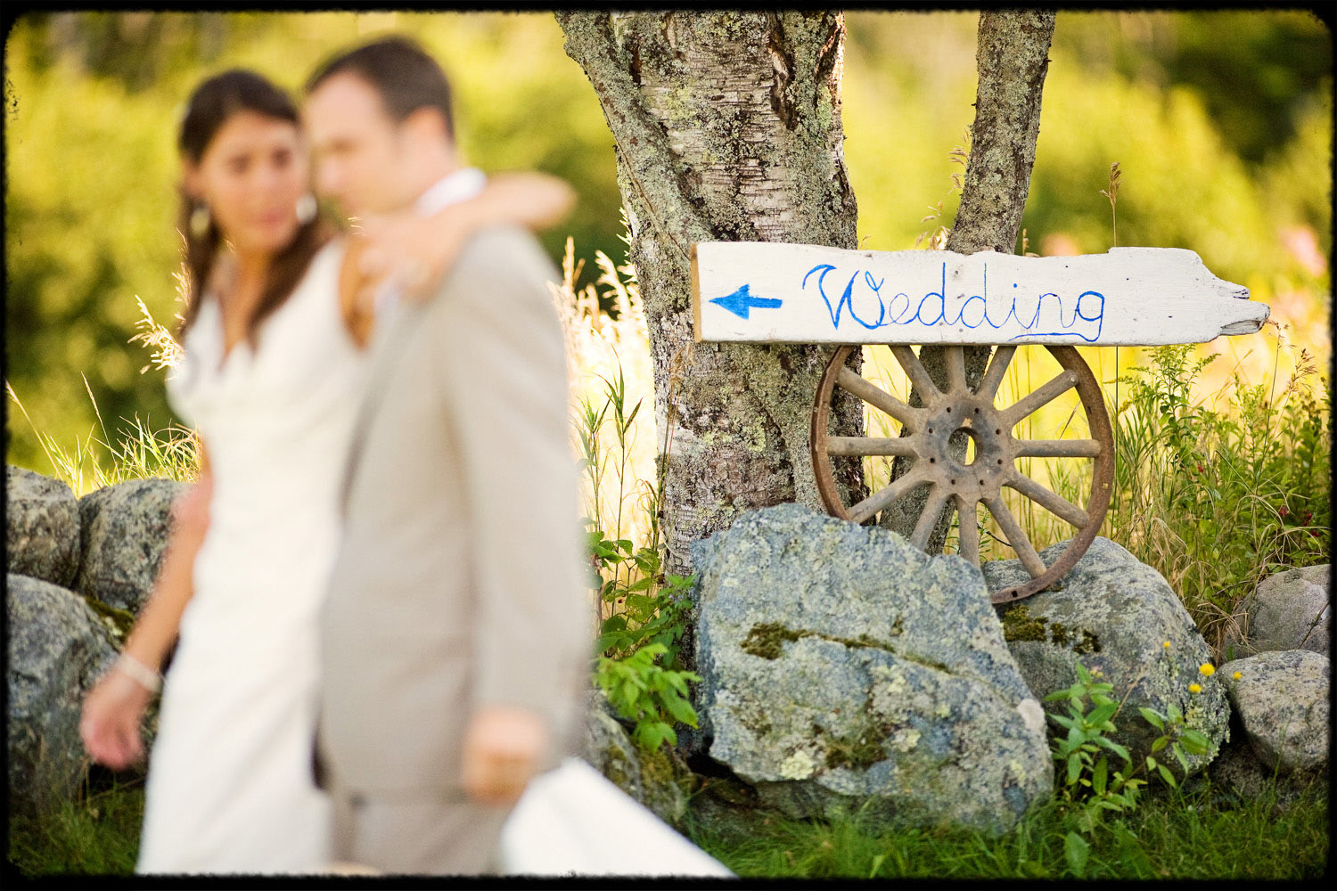 maine couple walks past wedding sign at barn