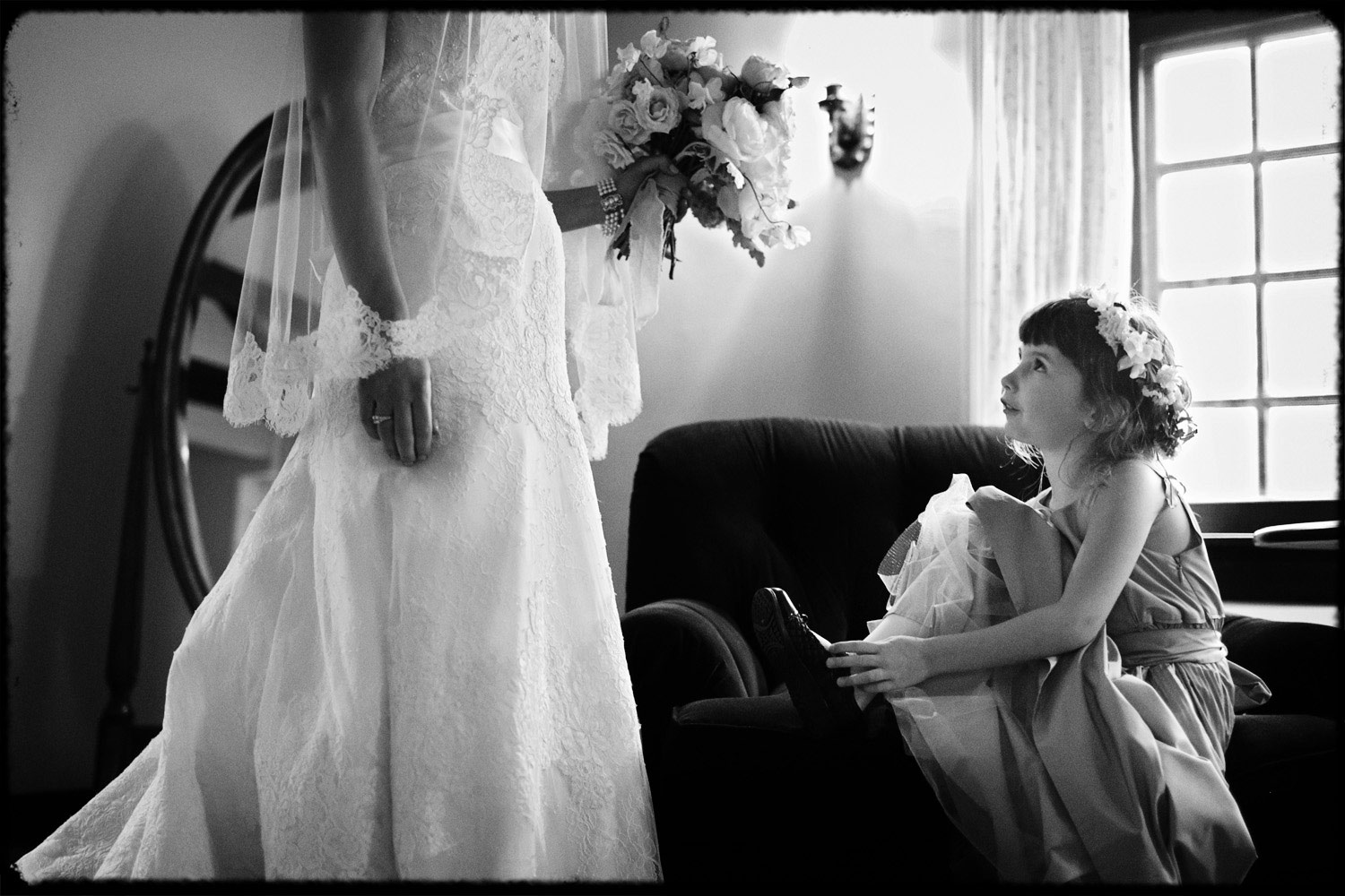 flower girl tying shoes while watching bride