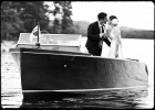 wedding couple kisses on chris craft boat on lake