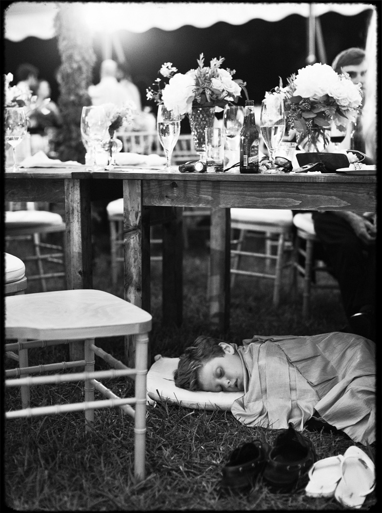 ringbearer sleeps under table at wedding reception
