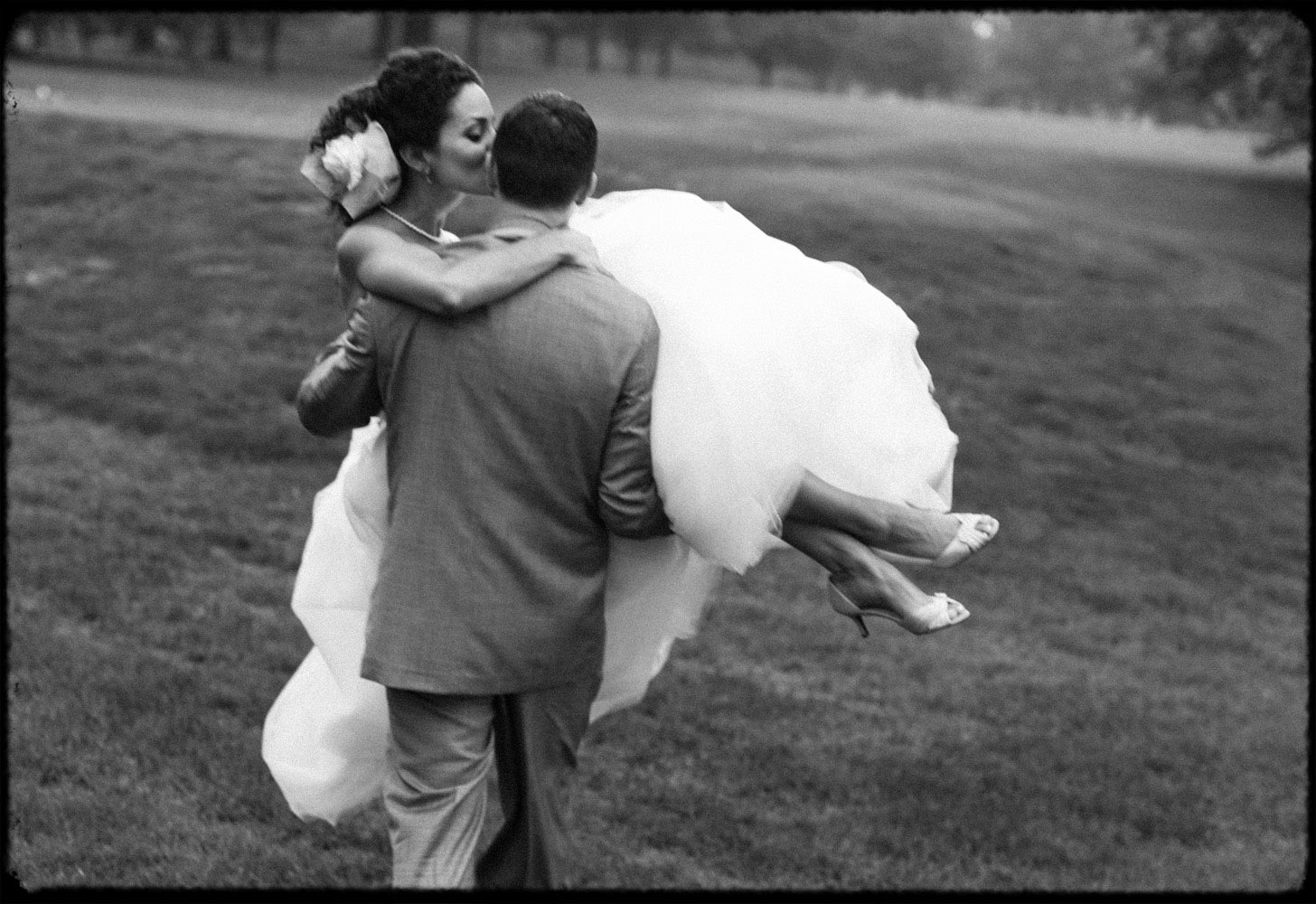 Black and white photo of groom carrying bride over wet golf course at York Country Club in Pennsylvania.
