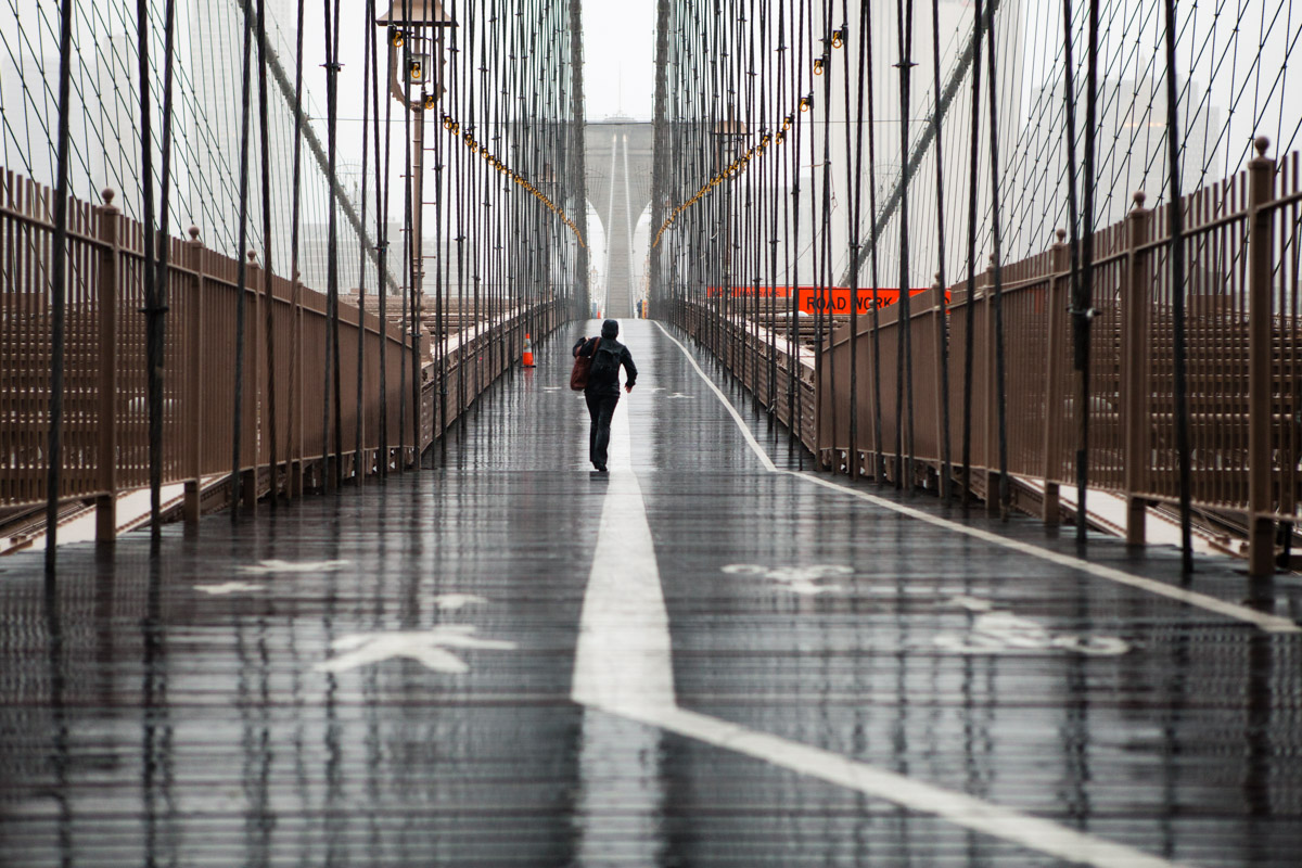 A woman cautiously makes her way across the Brooklyn Bridge as Hurricane Sandy approaches New York City. October 29, 2012.