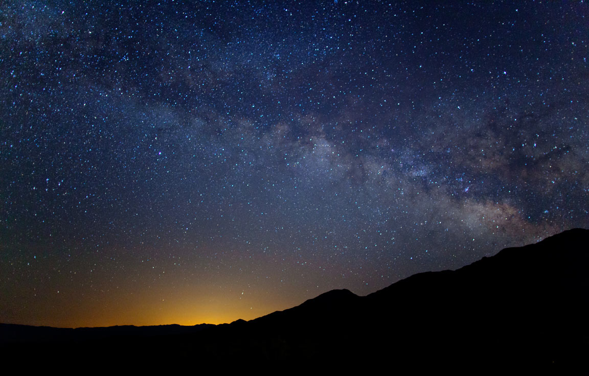 The Milky Way lighting up the nights sky. Las Vegas' lights can be seen in the distance. - Death Valley, CA