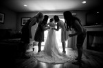 bridesmaids tying the bride's dress.