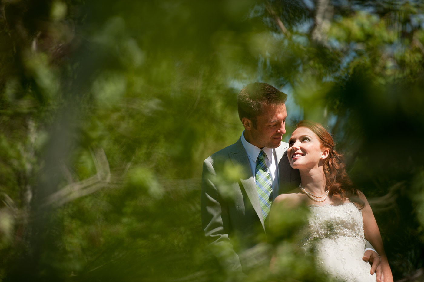 bride and groom embracing in the forest.