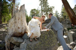 groom helping bride down from rock.