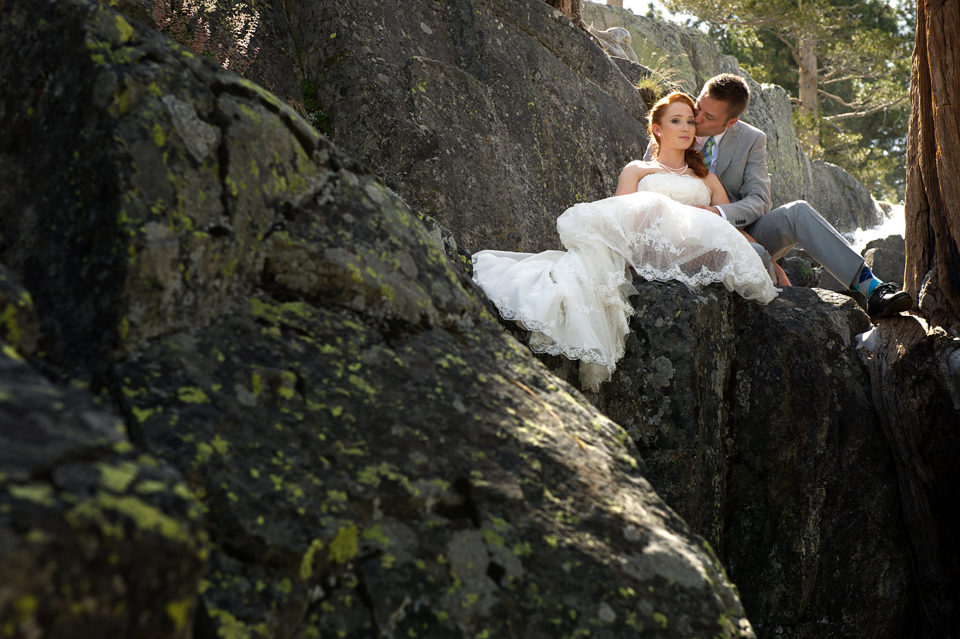 groom kissing bride near a waterfall.