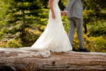 groom and bride holding hands on a log.
