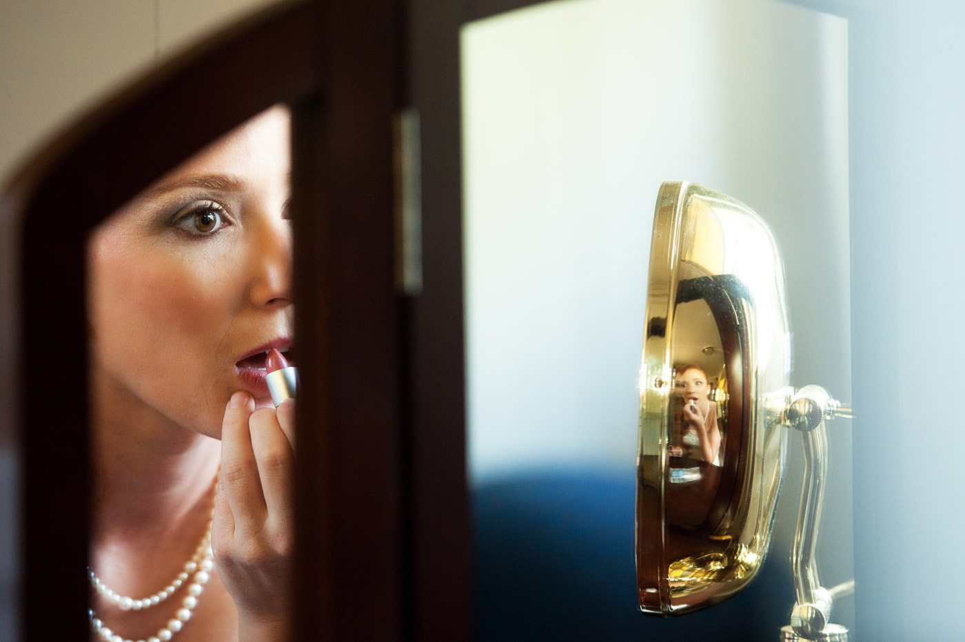 bride putting on lipstick in the mirror.