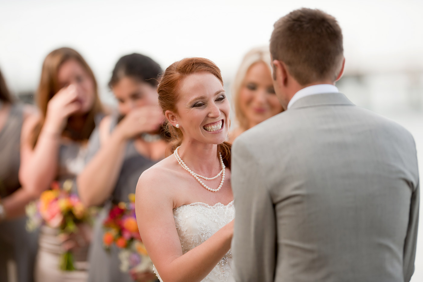 bridesmaids crying next to bride during ceremony.