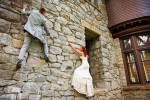 bride and groom climbing side of stone wall.