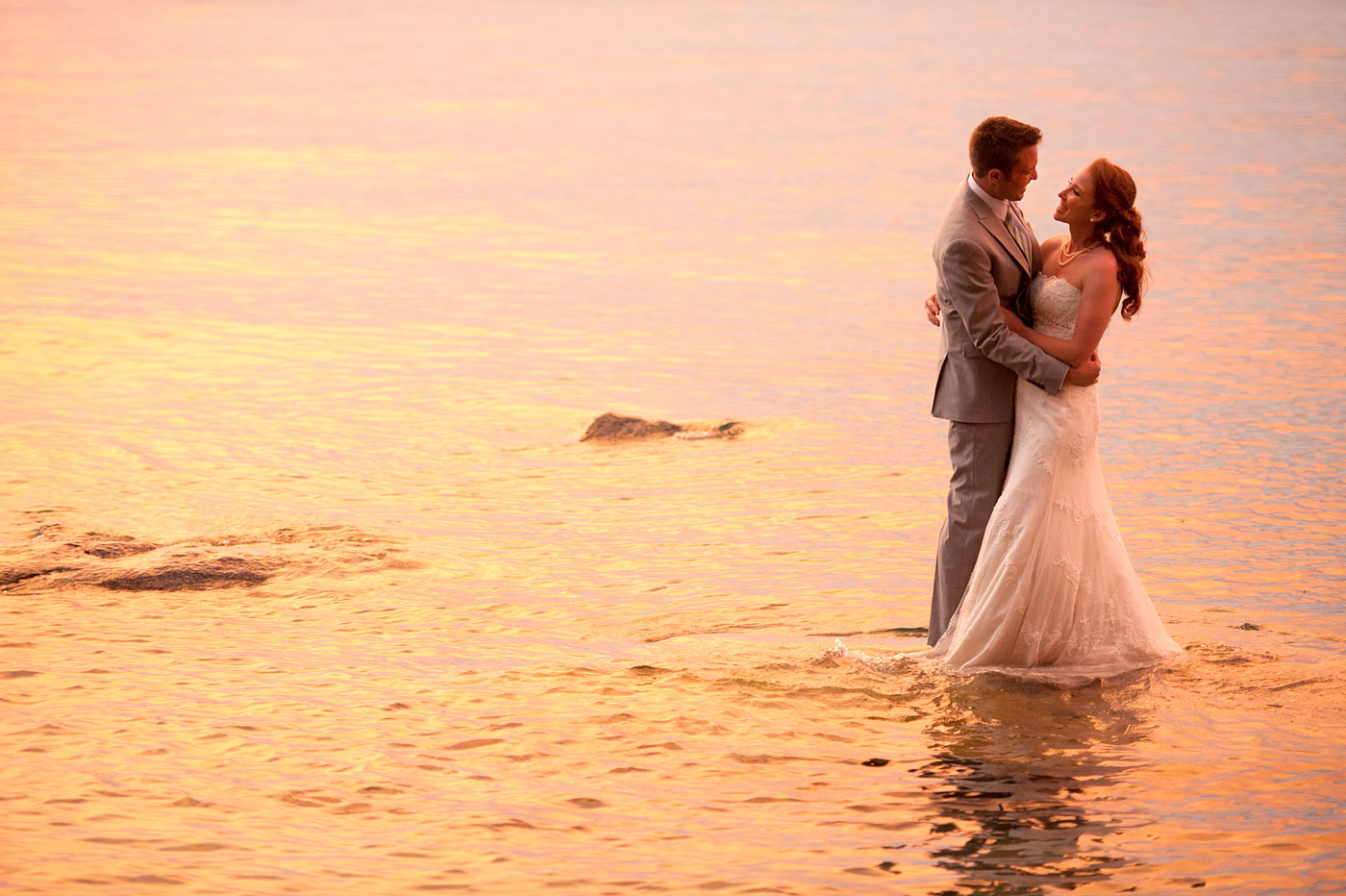 bride and groom embracing in lake at sunset.