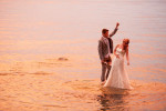 brides laughs as groom drops pants in the lake at sunset.