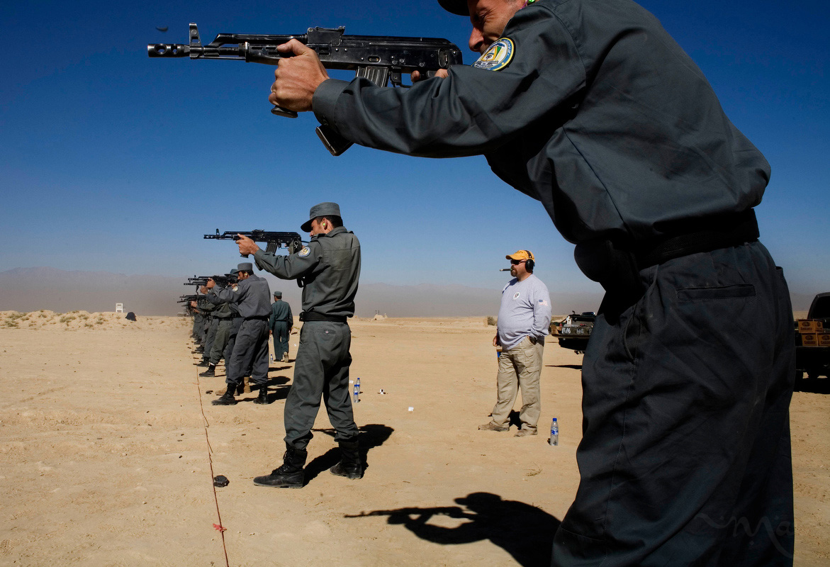 A DynCorp employee, center, monitors an Afghan police rifle course at a military range east of Kabul on Sunday October 21, 2007. The range is part of a Tactical Training Program (TTP) that is a follow-up and refresher to the first 8-week training the police received. The TTP gives Afghan police training in weapons, tactical movement as a team and classroom learning including criminal investigation training. Most of the classes are run by Afghan police teachers with mentoring and assistance by DynCorp employees.