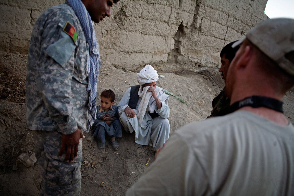 American soldiers watches as a villager who lost his house after the Americans dropped bombs on it the night before sheds tears. The villager alerted the Americans to the fact that the Taliban where holed up in his home. The Americans then bombed the home the following night. The man now was asking for compensation as everything he owned was destroyed in the attack. He now lives outside of town in a tent and was asking for food and clothing for this children.