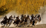 Riders chase down the man with the calf as they try to prevent him from dropping it in the circle during a game of Buzkashi in Khenj, Afghanistan on Friday, October 26, 2007. Each time a rider successfully completes the task he is cheered by the village and wins money.