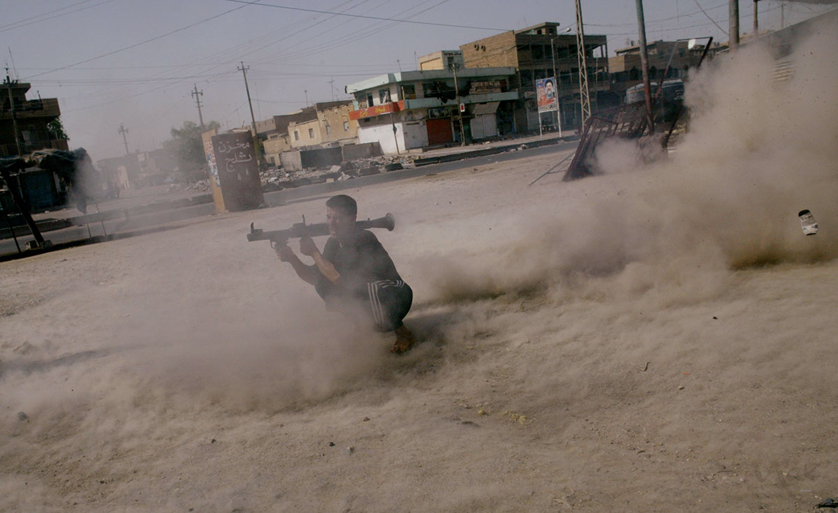A member of cleric Muqtada al-Sadr's Mehdi Army fires a rocket propelled grenade at a U.S. Army tank, which has taken up position on the south side of Sadr City. Clashes between the Mehdi Army and the U.S. military continued today in Sadr City as maneuvers were being made to end the standoff in Najaf between al-Sadr and the new Iraqi government.