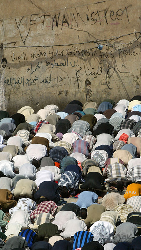 In front of a wall painted with the message, {quote}Vietnam Street: We'll make your graves in this place..{quote} thousands of Shia men participate in midday prayers around the streets of Moqtada al-Sadr's al Hekma Mosque. Sheikh Nasr al Sadr gave the sermon, which complained that the Allawi government and the U.S. were breaking the peace agreement that was signed in Najaf by storming a religious school in Najaf and disrespecting al-Sadr clerics. His sermon went on to list several other grievances but only hinted at any retaliation for these issues.