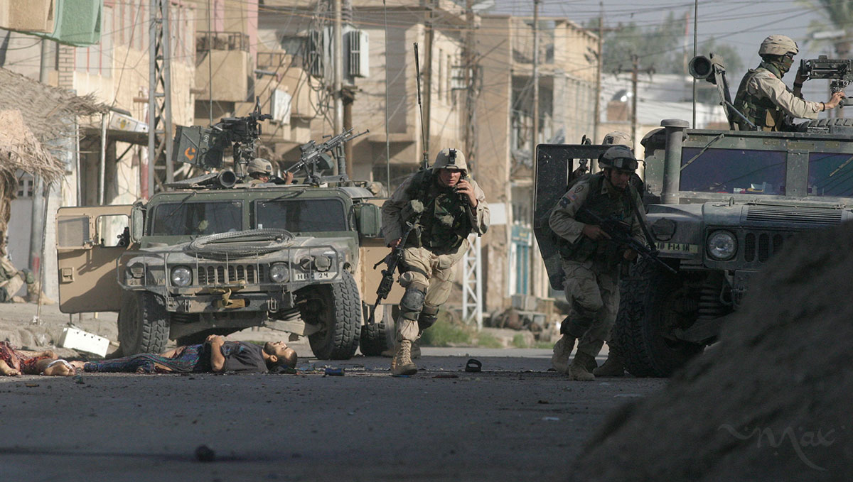 U.S. soldiers with the 25th Infantry Division, 1st Battalion, 14th Regiment, Alpha Company, who are attached to the 1st Infantry Division, advance past the bodies of insurgents killed during the attack to take back Samarra from insurgent control. The operation circled the city of Samarra with four battalions.