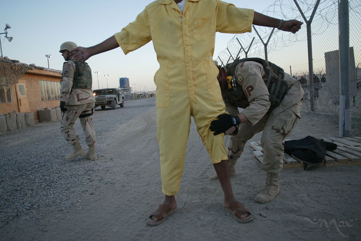 Corporal Scott Horton pats down a prisoner to take him to a family visitation session at Camp Redemption in the Abu Ghraib prison complex. Once detainees greet their visitors, the U.S. solders will take a digital photo of them together and hand them the images before they leave.