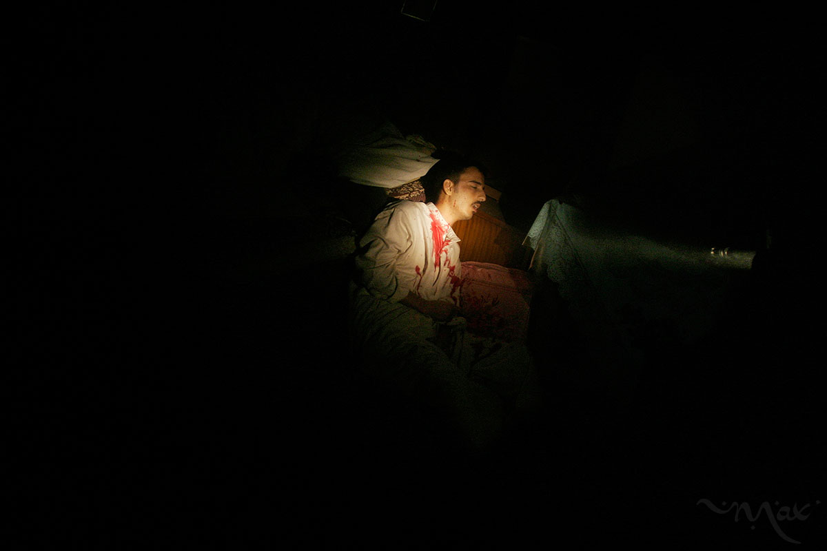 The light from a Marine's rifle illuminates a man he shot during house to house fighting in Fallujah, Iraq.