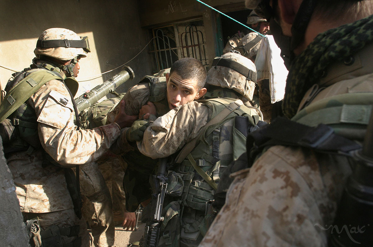 Marines help Lance Corporal Enrique Mayer who was shot in the leg after being ambushed by insurgents. After fleeing the ambush Mayer found shelter in the home behind him. Mayer lay bleeding as the firefight raged. After the insurgents were killed Mayer was lifted out of the house when he became dizzy because of his blood loss and fell on his fellow Marines.