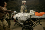 A wounded soldier and fellow Marine sent as care taker rush to the emergency room of the Air Force Theater Hospital in Balad, Iraq on August 27, 2005.