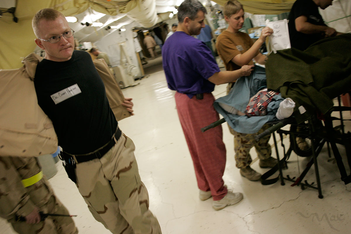 Emergency room doctor, Major Corey Harrison at the Theater Medical Hospital, run by the 332nd Expeditionary Medical Group, takes his flak vest off as he rushes to treat wounded American soldiers in Balad, Iraq on October 30, 2005.