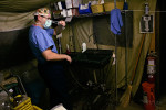 Colonel Elisha Powell the commander of the Theater Medical Hospital of the 332nd Expeditionary Medical Group, at Balad Air Base takes his mask off and cleans up in the field and tent operating room where he prepares wounded soldiers for their flight to Germany for more advanced surgery.