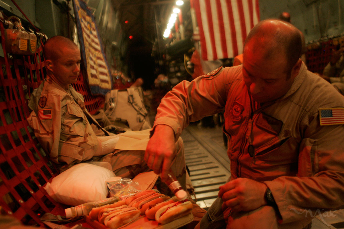 Flight medical technician, Staff Sergeant Judd Everly from the 94th Aeromedical Evacuation Squadron serves hot dogs to wounded soldier Staff Sergeant John Carroll, who has a broken hand, during the flight of a C-141 medical transport from Balad Air Base in central Iraq to Landstuhl  Regional Medical Center in Germany where he will receive treatment. The flight medics try to make sure the wounded have all of their medical and comfort needs taken care of during the flight.