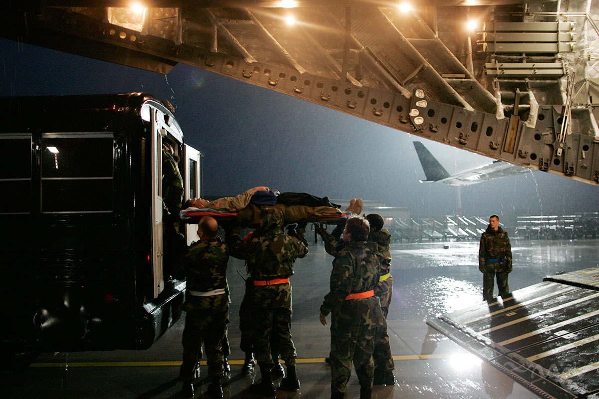 A wounded soldier is carried off of a C-17 aircraft to a rainy flight line at Ramstein Air Base after taking a five-hour flight from Iraq. Soldiers are transported on a C-17 plane from Iraq to Ramstein Air Force Base in Germany. The wounded are then transported to buses and driven to the Landstuhl Regional Medical Center where their wounds will be further repaired, cleaned and treated. By the time the wounded reach Germany they face mainly operations of recovery as opposed to life saving operations.