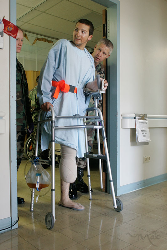 Physical Therapist Maj. Ford David Paulson helps Marine Lance Corporal Matthew Schilling choose which stretch of the hallway to tackle, the short way or the long way, as Schilling takes his first walker-assisted steps at the Landstuhl Regional Medical Center. Schilling chose to take the longer trip. Schilling returned to his bed exhausted but satisfied that with a modern prosthetic limb, he would be able to walk again. Once back in the United States Schilling will join the ranks of approximately 5,557 soldiers who have suffered wounds in Iraq in the year 2005 alone. Some 15, 955 have been wounded since the start of the war according to information released by the United States government.