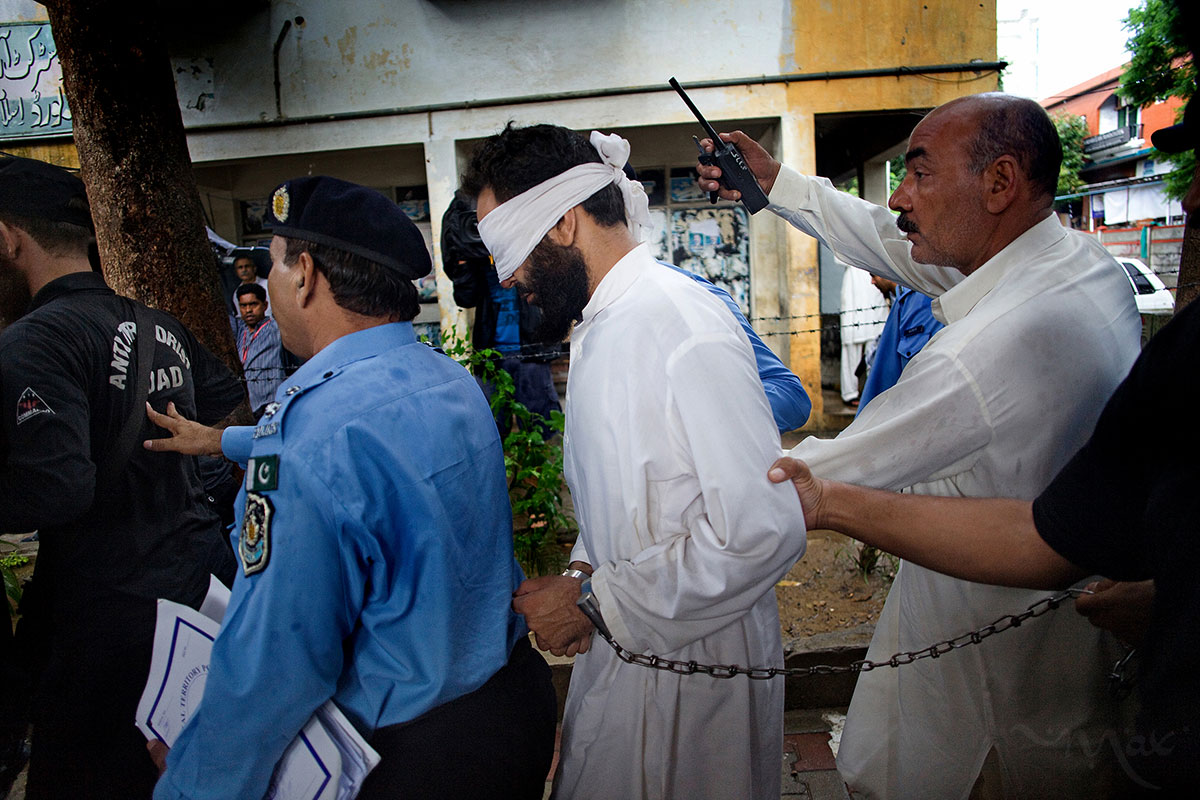 ISLAMABAD, PAKISTAN. Imam Hafiz Mohammed Khalid Chishti is blindfolded and shackled as he is led to court to receive formal charges for falsely accusing a young Christian girl of burning pages of the Quran at the Islamabad District Court in Islamabad, Pakistan on Sunday September 2, 2012. The Imam was arrested after his deputy made a statement saying he saw the Imam add pages to the burning ashes in order to accuse the girl of blasphemy and expel the Christian family from the neighborhood. The case involves Rimsha Masih who was arrested on August 16, 2012 on charges of blasphemy after being accused of burning pages of the Quran by a crowd of her Muslim neighbors. The girl, who is believed to be between the ages of 11 to 14, and her family were roughed-up by the crowed before being taken into custody by the police.