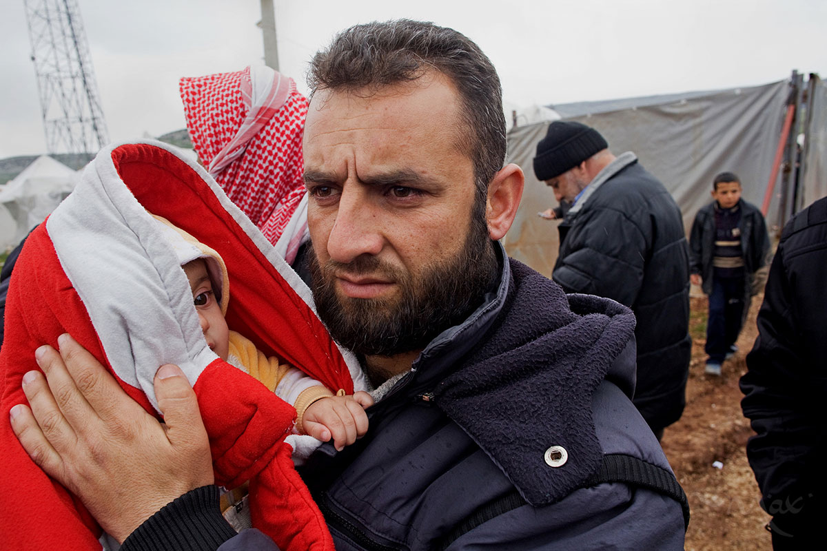 A Syrian man holds his son who is bundled up against the cold in the Reyhanli refugee camp in Hatay province on the Turkish/Syrian border on Friday March 16, 2012.