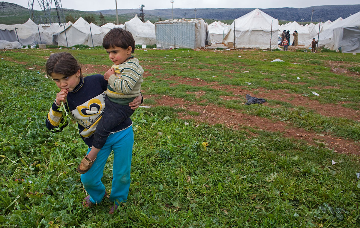 A young girl eats vegetables picked from the field as she holds a child outside the Reyhanli refugee camp in Hatay province on the Turkish/Syrian border on Friday March 16, 2012. Turkey is sheltering more than 13,000 people in seven camps managed by the government.