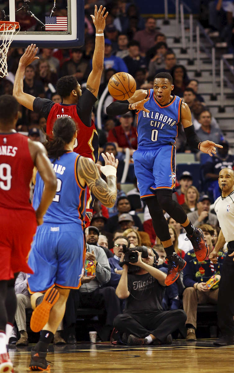 Oklahoma City Thunder guard Russell Westbrook (0) makes a pass to center Steven Adams, second from left, around New Orleans Pelicans forward Anthony Davis, third from left, in the second half of an NBA basketball game in New Orleans, Wednesday, Dec. 21, 2016. (AP Photo/Max Becherer)