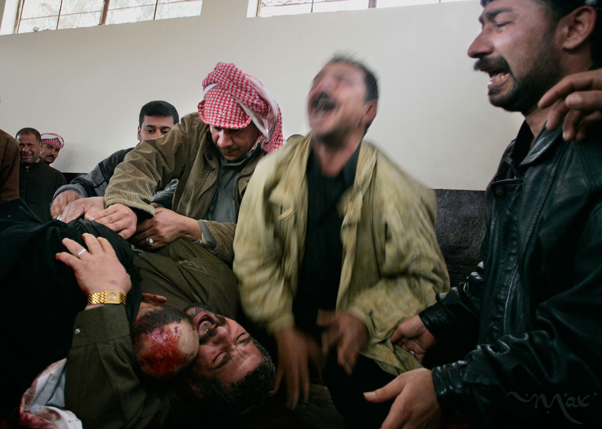 Karim Rahim Judi Yacoubi, bottom left, holds the corpse of his dead brother, Naim, 37, as he and his brothers, Salim, center in a green jacket, and Hadi, right, scream out in grief in the washroom where Naim's body was being prepared for burial in the Najaf cemetery. Naim was killed during a suicide bombing on Election Day in Baghdad.