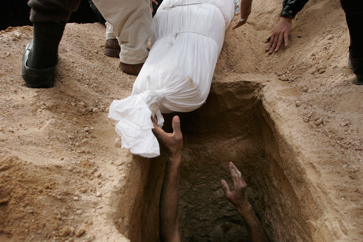 A gravedigger reaches for the body of, Naim Rahim Judi Yacoubi, 37, to lower him into his grave. While many Iraqis were joyous to have the opportunity to vote, others paid the ultimate price.