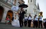 NEW ORLEANS, LOUISIANA. Newlyweds Todd Ledet and Megan Bendig dance their way out of St. Louis Cathedral at Jackson Square in the French Quarter of New Orleans, Saturday, Aug. 15, 2015. Hurricane Katrina put roughly 80 percent of the New Orleans under water. Hundreds of people drowned inside their homes, their bodies floating in the muck. Hospitals and police were overwhelmed. The city emptied. Now, as people describe the city's resurgence, they reach for metaphors that verge on the Biblical: a resurrection, an economic and cultural renaissance, a rebirth. (AP Photo/Max Becherer)