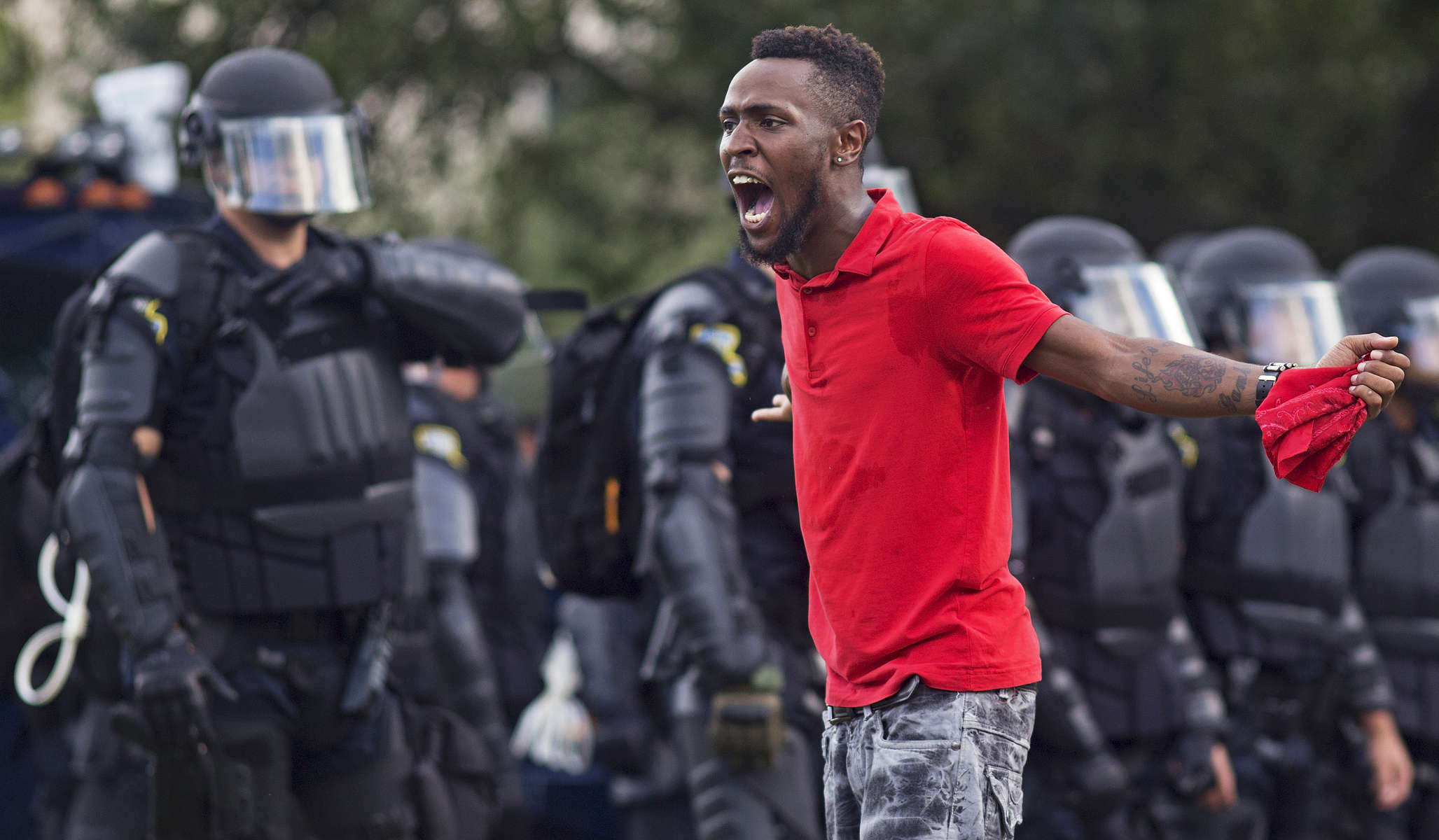 A protester yells at police in front of the Baton Rouge Police Department headquarters after police arrived in riot gear to clear protesters from the street in Baton Rouge, La. USA, Saturday, July 09, 2016. The starting point of Saturday's demonstration was the convenience store where 37-year-old Alton Sterling, a black CD seller, was captured on video being shot and killed by white police on July 5th. Protesters then fanned out to the Baton Rouge Police Department and the State Capitol. (AP Photo/Max Becherer)