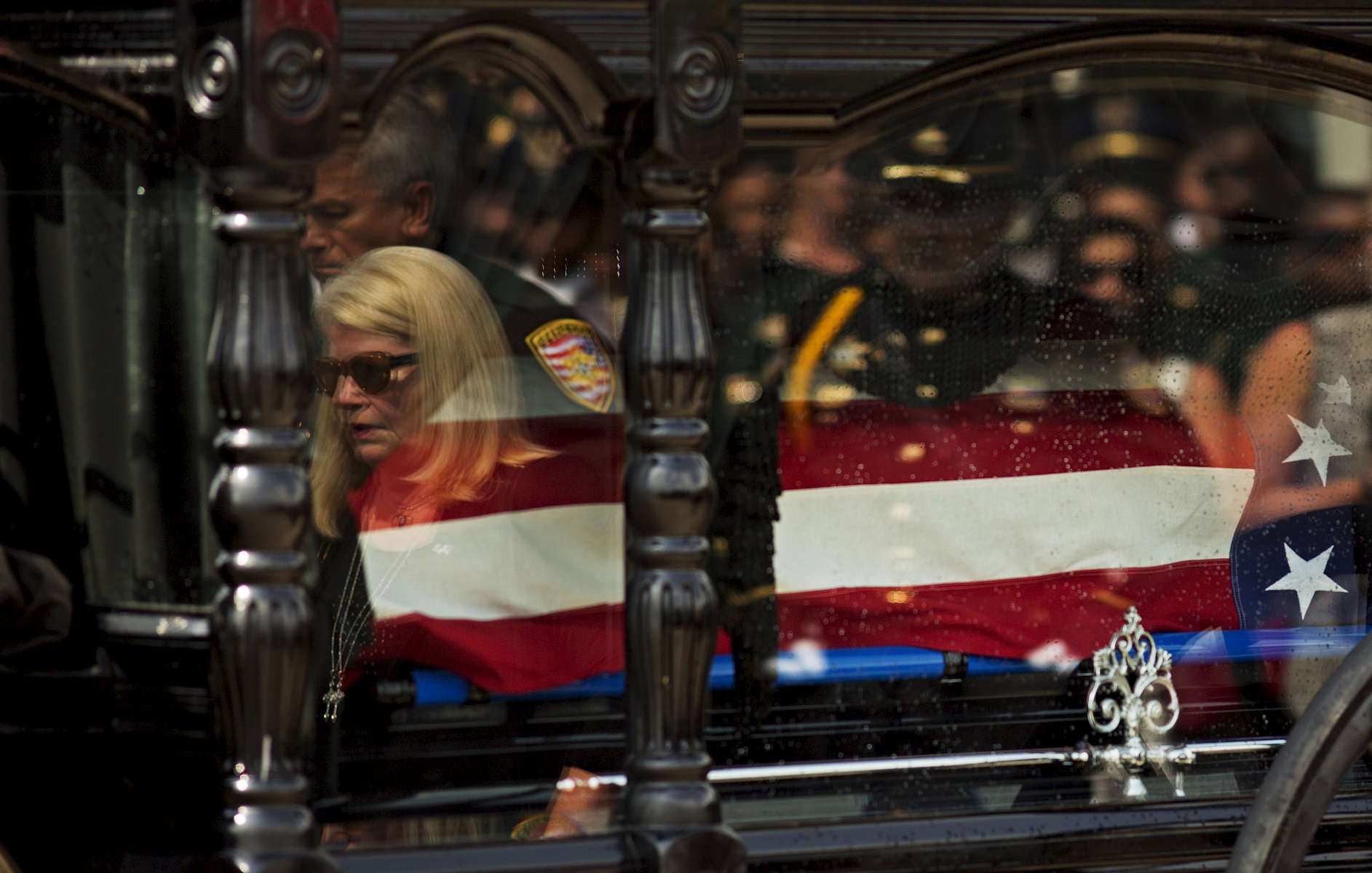 East Baton Rouge Parish Sheriff Sid  Gautreaux and his wife are reflected in the glass of the horse-drawn carriage carrying the casket of East Baton Rouge Sheriff's Deputy Brad Garafola at the Istrouma Baptist Church in Baton Rouge, La. USA, Saturday, July 23, 2016. Garafola is survived by a wife and four children; sons ages 21 and 12; and daughters ages 15 and 7. {quote}When that assassin's bullet targeted our heroes — and he was an assassin — he not only targeted them, he targeted the city. He targeted his country, and it touched the soul of the entire nation,{quote} Vice President of the United States Joe Biden said at a memorial for the three slain officers six days later. (Max Becherer/AP)