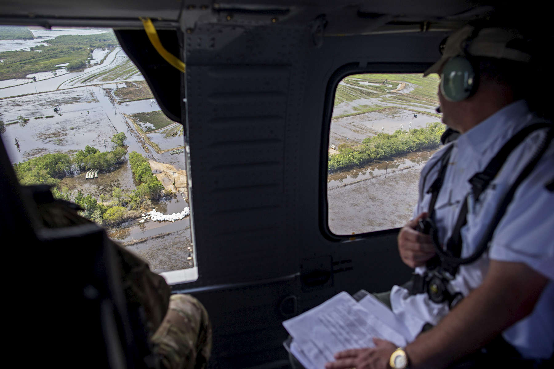 Louisiana Gov. John Bel Edwards, right, reviews a shored up breach in a levee dam that the Louisiana National Guard filled using 362, 4000-lb. sand bags that were put in place with a helicopter near Gueydan, La. USA, Thursday, Aug. 25, 2016. {quote}Though we are bringing to bear all the FEMA relief we can and what's allowed by statute, it's not going to be enough to make people whole, and that's unfortunate,{quote} Louisiana Gov. John Bel Edwards said. (AP Photo/Max Becherer)