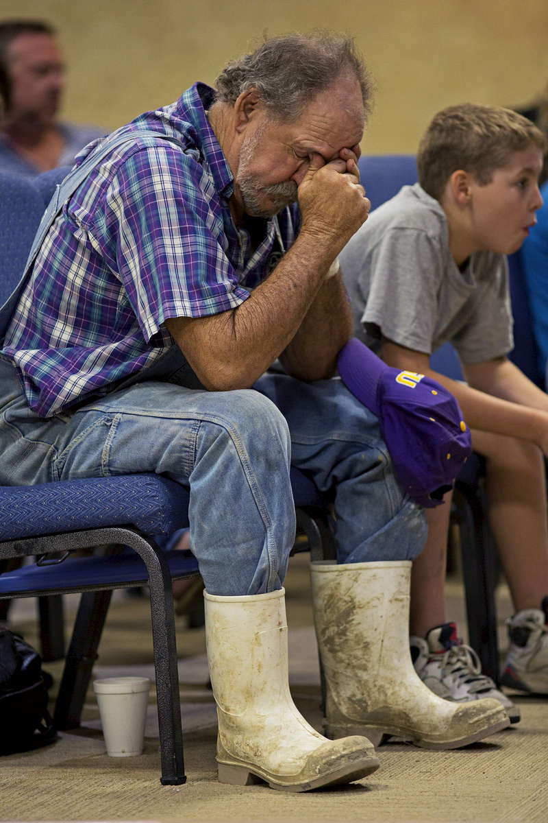 Robert Miller, 66, prays during service at the South Walker Baptist Church in Walker, La. USA, Sunday, Aug. 21, 2016. Miller had six family members in his home when the flood struck and helped them flee the home while he stayed behind to care for his dogs. Miller wounded his left wrist with a saw while trying to clean up the flood damage. (AP Photo/Max Becherer)