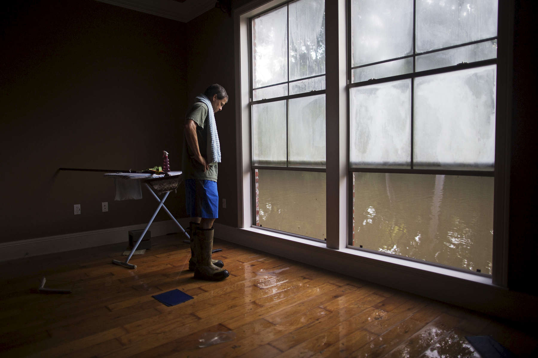 David Key looks at water out of his master bedroom windows in his flooded home in Prairieville, La. USA, Tuesday, Aug. 16, 2016. Key, an insurance adjuster, fled his home as the flood water was rising with his wife and three children and returned Tuesday to assess the damage. Mike Steele, spokesman for the Governor's Office of Homeland Security and Emergency Preparedness, said 102,000 people have registered for federal aid. (AP Photo/Max Becherer)