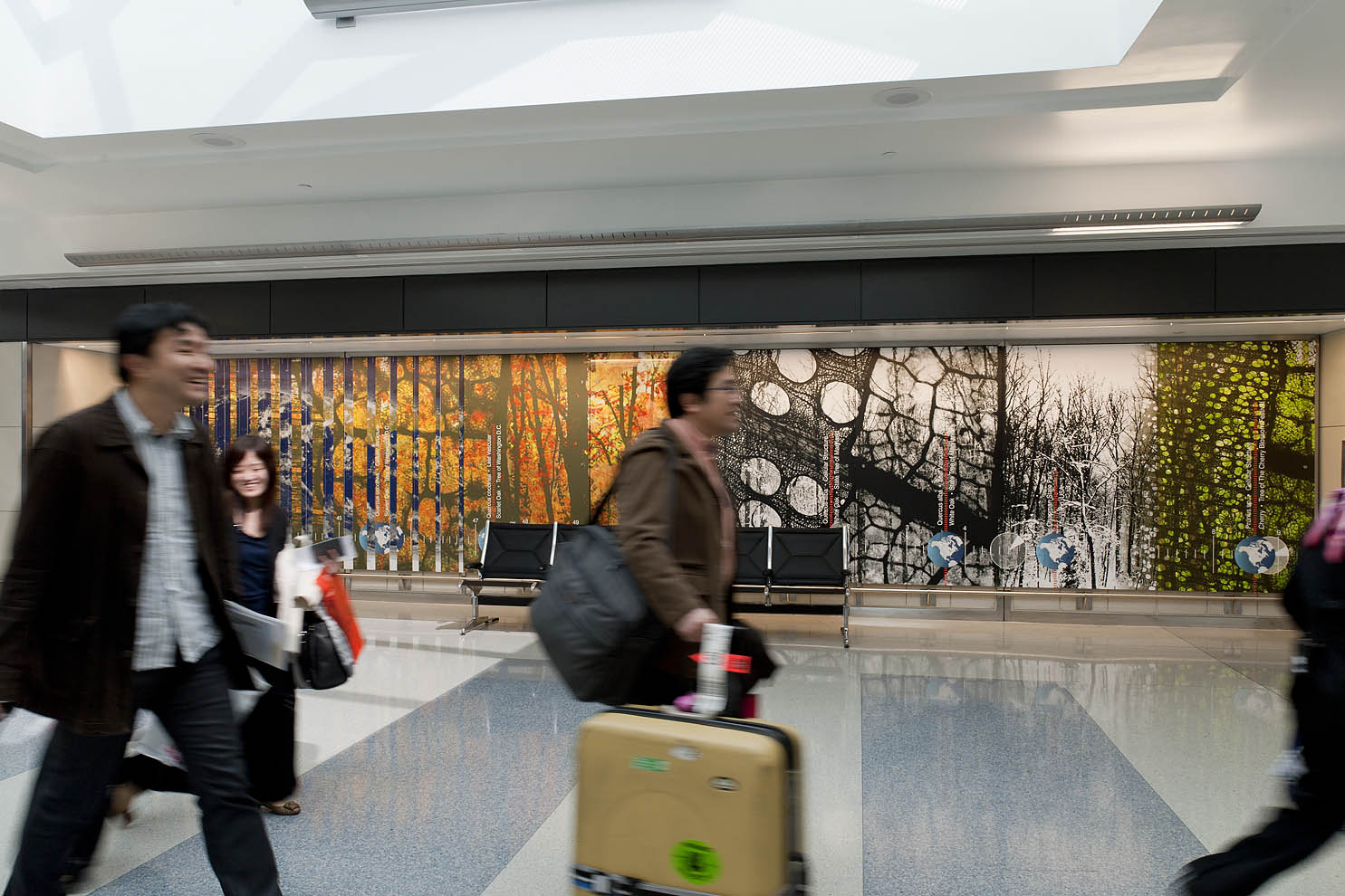 arriving passengers walking past art wall