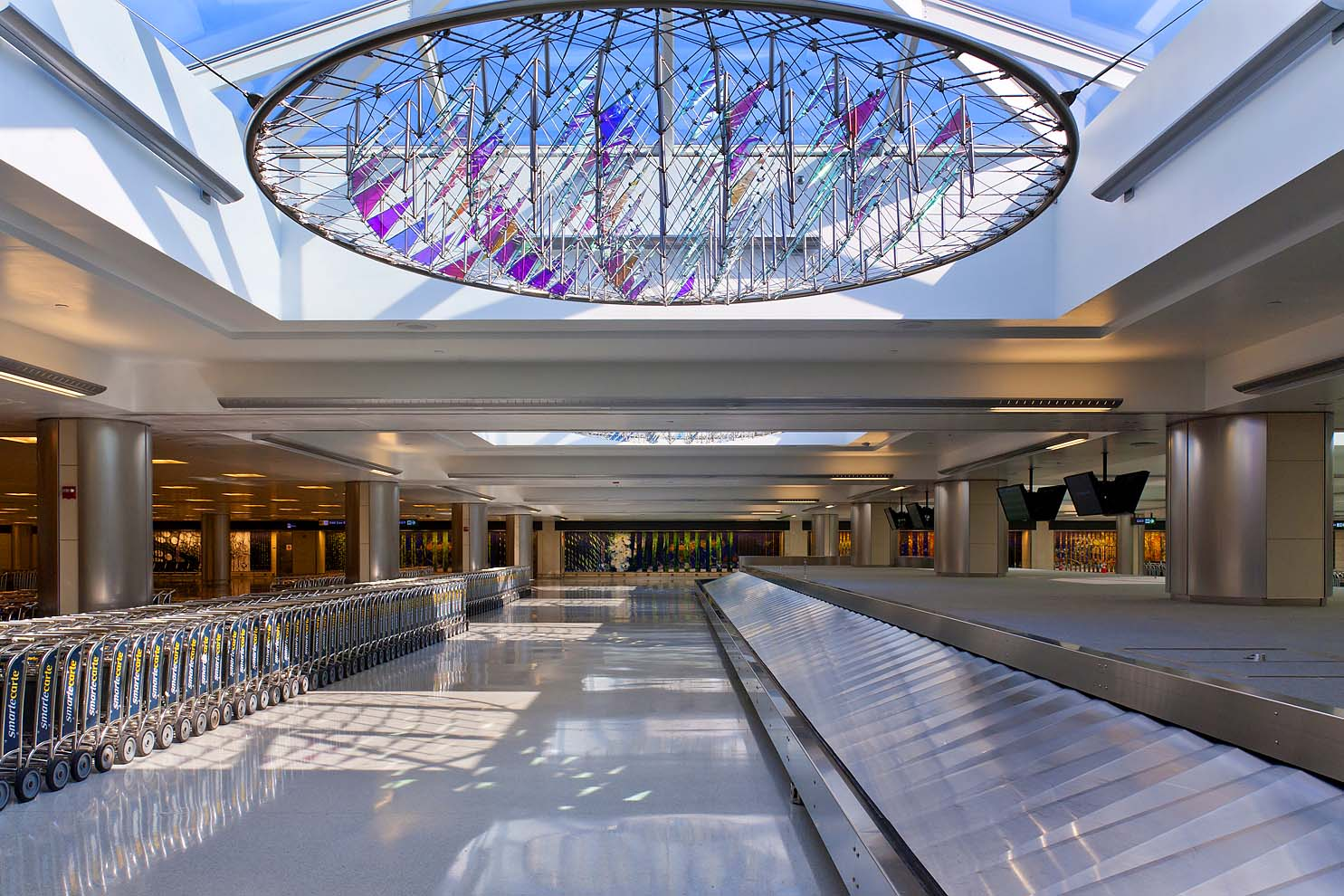 dichroic glass sculpture in skylight next to baggage carousel