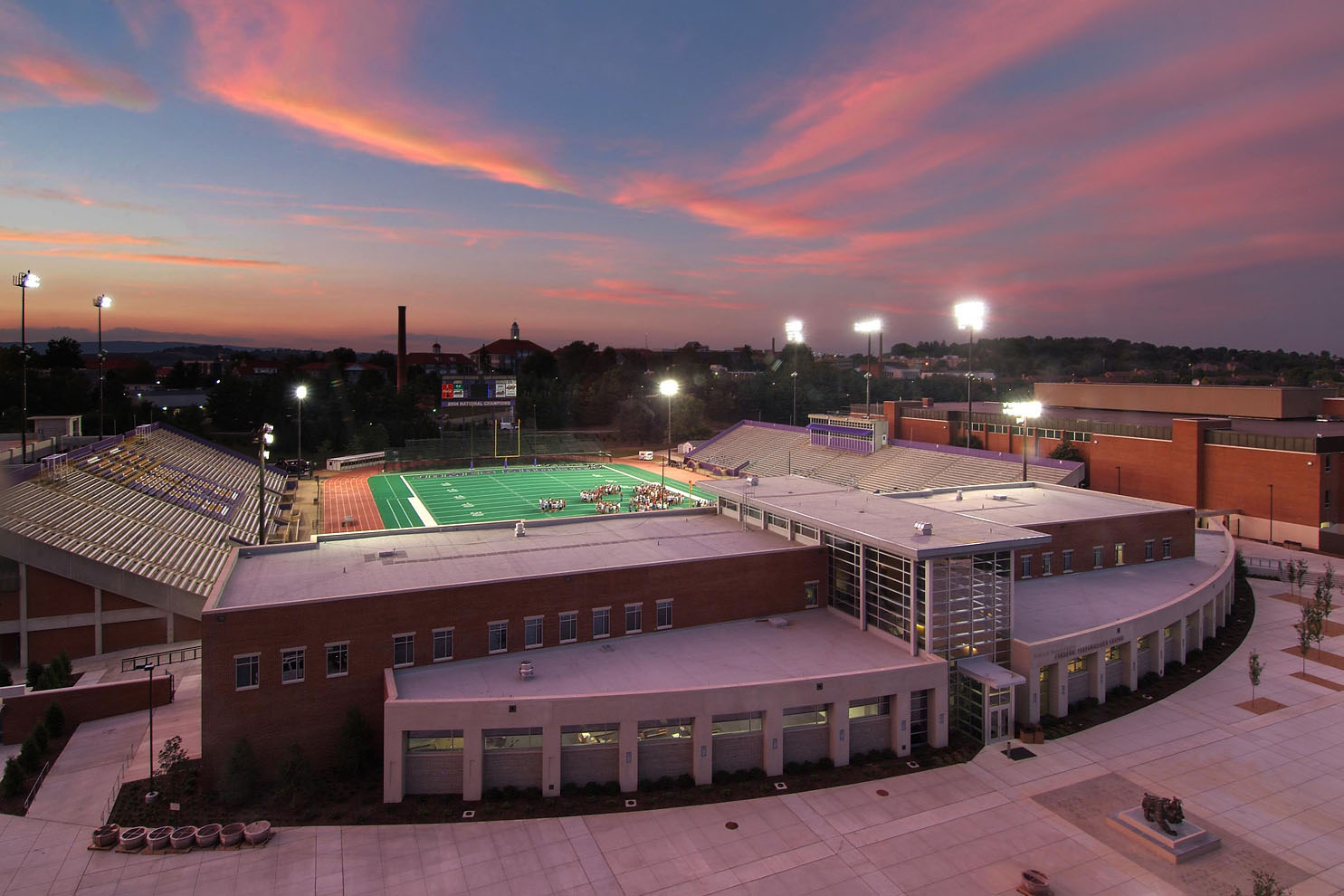 twilight view of building and football field beyond